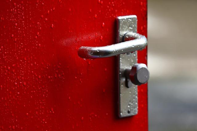 stříbrná klika na červených dveřích